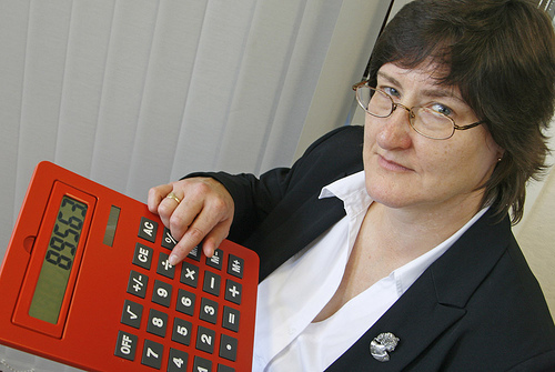 image of a brown haired woman with glasses holding a silly oversized calculator